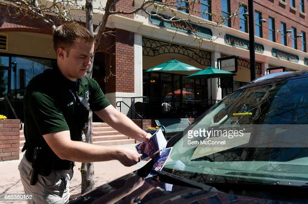 Neighborhood Service Officer Ryley Davis places information pamphlets on the new parking restrictions on the windshields of cars along Main Street on...