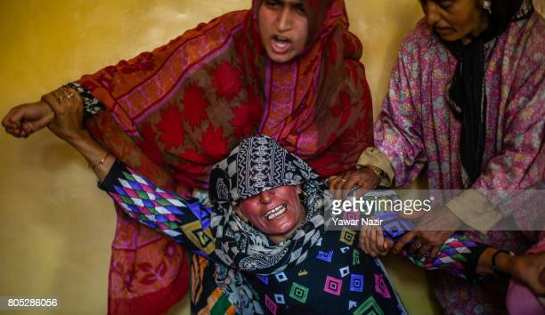 Neighbors and relatives console the sister of Tahira Begum a civilian after she was killed near the gun battle site on July 01 2017 in Dialgam 70 km...