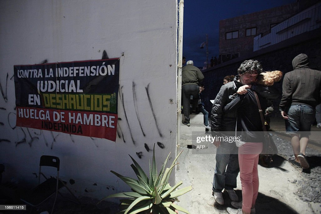 Neighbors hug before the arrrival of Spanish Guardia Civil to evict them from their homes in the fishing village of Chovito on the Spanish Canary Island of Tenerife, on November 16, 2012. Six neighbors have been on hunger strike to protest a court decision requiring the demolition of their houses according to the Spanish Coastal Law.