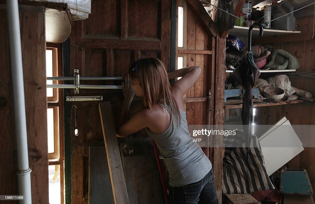 A neighbors locks the front door of her house before the arrrival of Spanish Guardia Civil to evict her from her home in the fishing village of Chovito on the Spanish Canary Island of Tenerife, on November 16, 2012. Six neighbors have been on hunger strike to protest a court decision requiring the demolition of their houses according to the Spanish Coastal Law.