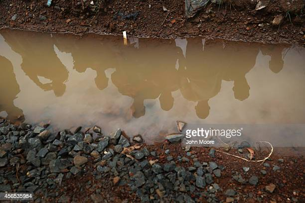 Neighbors watch as a burial team collects bodies of Ebola victims for cremation on October 2 2014 in Monrovia Liberia Eight Liberian Red Cross burial...