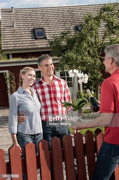 Neighbour greeting couple new home gift