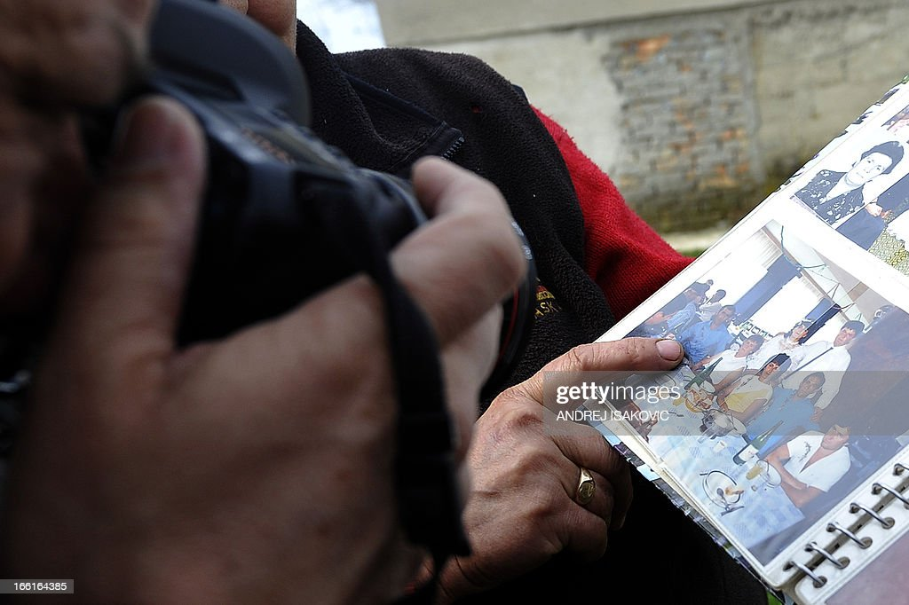 A neighbour shows a family album bearing a picture of the alleged killer in the village of Velika Ivanca, 40 kilometres south of capital Belgrade, on April 9, 2013, where a man shot dead 13 relatives and neighbours, including a two-year-old child, in the country's worst killing spree in two decades..