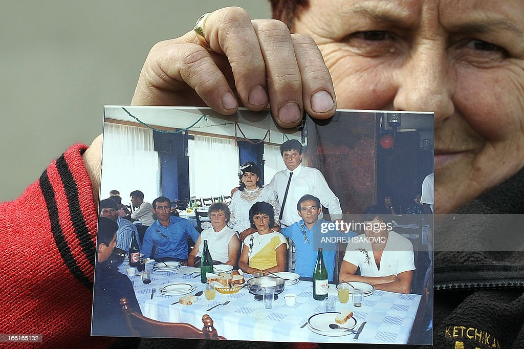 A neighbour shows a family album bearing a picture of the alleged killer (7thR) in the village of Velika Ivanca, 40 kilometres south of capital Belgrade, on April 9, 2013, where a man shot dead 13 relatives and neighbours, including a two-year-old child, in the country's worst killing spree in two decades..