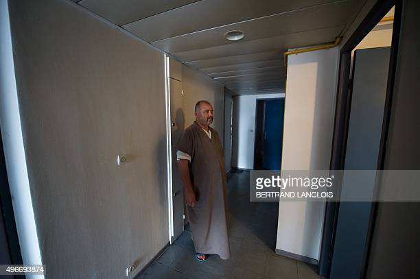 A neighbour stands outside the apartment of a man who was arrested after being suspected of having links to an Islamic State group jihadist in Syria...