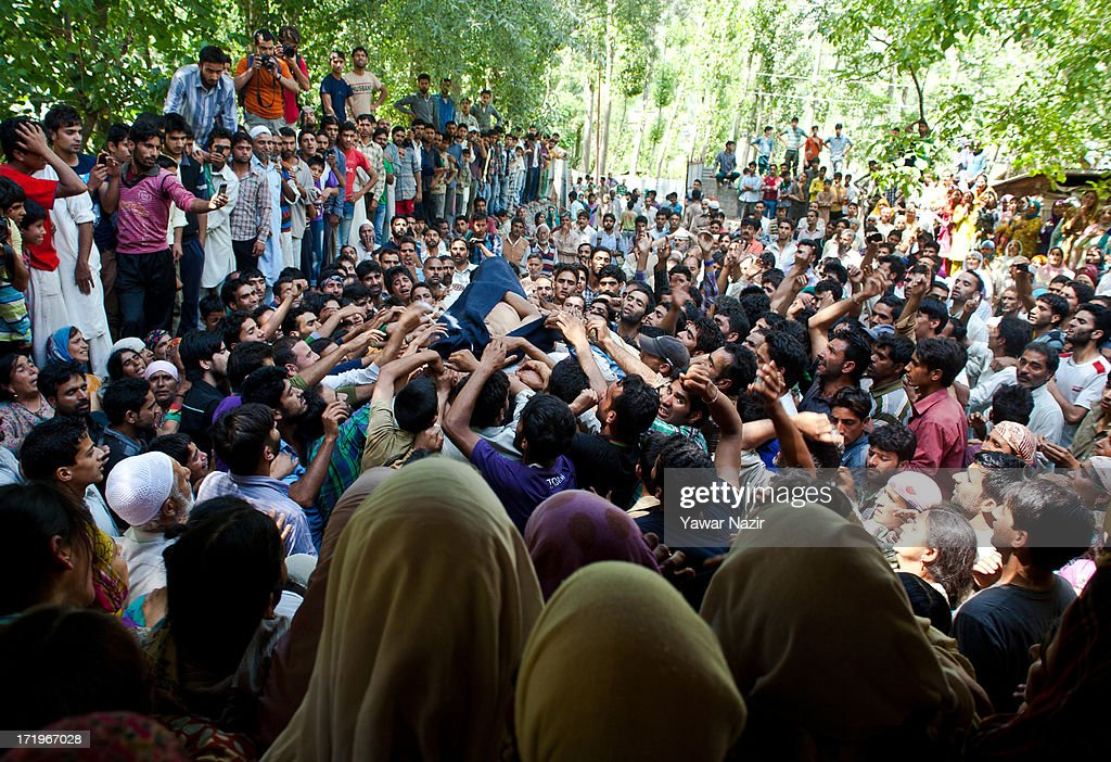 Neighbours and relatives carry the body of Tariq Ahmed, a civilian who was killed by Indian army, during his funeral on June 30, 2013 in Kondebal 25 km (15 miles) north of Srinagar the summer capital of Indian administered Kashmir, India. A teenage boy, identified as Irfan Ahmad Ganaie was killed during a search operation by Indian police in the village of Markondal in Bandipora District, before dawn on Sunday. A second person, Tariq Ahmad Leharwal, was killed after the Indian army shot at local residents who were protesting the earlier deadly incident. The killings triggered mass protests in the area.