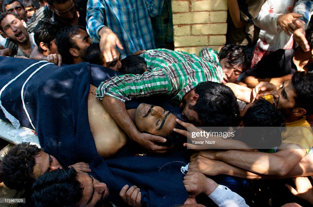 Neighbours and relatives of Tariq Ahmed, a civilian who was killed by Indian army, mourns over his body during his funeral on June 30, 2013 in Kondebal 25 km (15 miles) north of Srinagar the summer capital of Indian administered Kashmir, India. A teenage boy, identified as Irfan Ahmad Ganaie was killed during a search operation by Indian police in the village of Markondal in Bandipora District, before dawn on Sunday. A second person, Tariq Ahmad Leharwal, was killed after the Indian army shot at local residents who were protesting the earlier deadly incident. The killings triggered mass protests in the area.
