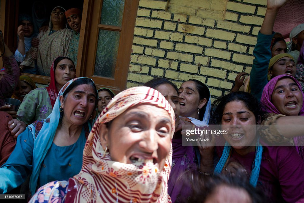 Neighbours and relatives of Tariq Ahmed, a civilian who was killed by Indian army, mourns during his funeral on June 30, 2013 in Kondebal 25 km (15 miles) north of Srinagar the summer capital of Indian administered Kashmir, India. A teenage boy, identified as Irfan Ahmad Ganaie was killed during a search operation by Indian police in the village of Markondal in Bandipora District, before dawn on Sunday. A second person, Tariq Ahmad Leharwal, was killed after the Indian army shot at local residents who were protesting the earlier deadly incident. The killings triggered mass protests in the area.