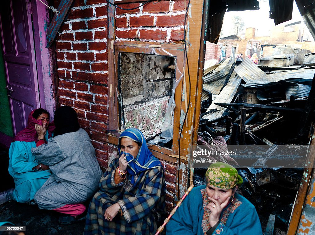 Neighbours console Kashmiri women as after a fire gutted many residential houses on December 30, 2012, in Srinagar, the summer capital of Indian administered Kashmir, India. Many families were left homeless amid sub-zero temperatures during the harshest 40-day period (Chilay Kalan) of the winter, after at least 30 residential houses were damaged in a devastating fire on the bank of famous Dal Lake near the Hazratbal shrine, in the outskirts of the Srinagar. The incident engulfed the area during the preceding night, an official said. No injuries were reported.