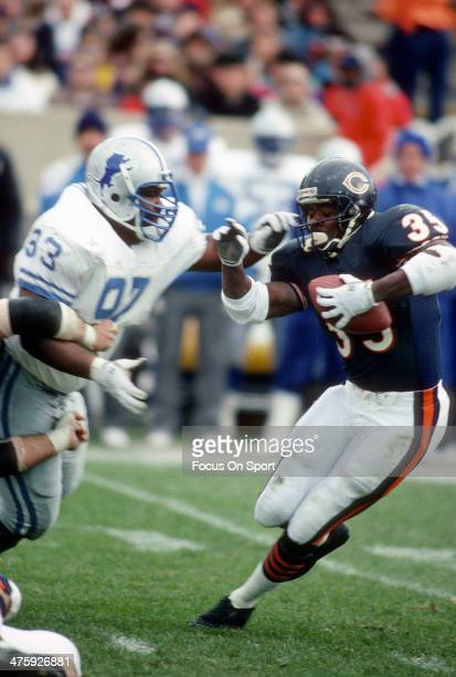 Neil Anderson of the Chicago Bears carries the ball and is pursued by Jerry Ball of the Detroit Lions during an NFL Football game December 2 1990 at...