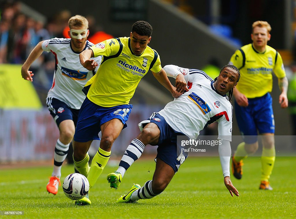 Neil Danns of Bolton Wanderers tackles Tom Adeyemi of Birmingham City during the Sky Bet Championship match between Bolton Wanderers and Birmingham City at Reebok Stadium on May 3, 2014 in Bolton, England.