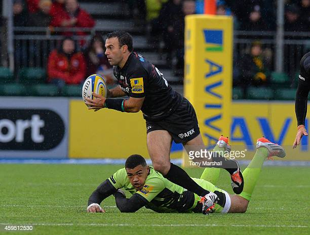 Neil de Kock of Saracens races away as Luther Burrell of Northampton Saints looks on during the Aviva Premiership match between Saracens and...