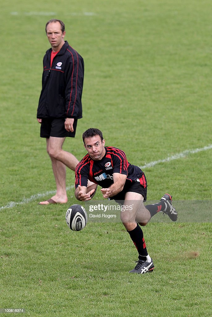 Neil de Kock passes the ball watched by coach Brendan Venter during the Saracens training session on May 25, 2010 in St Albans, England.