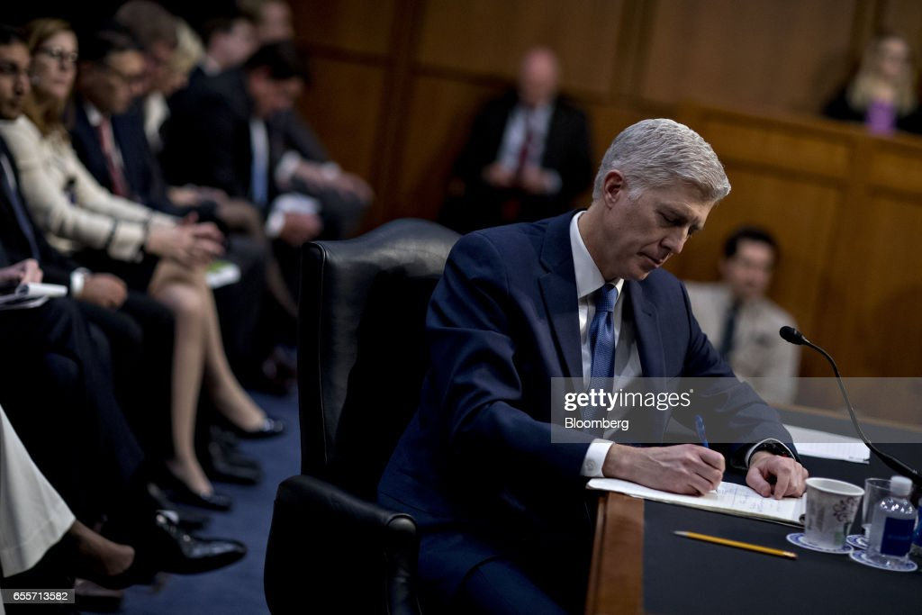 Neil Gorsuch, U.S. Supreme Court nominee for U.S. President Donald Trump, takes notes during a Senate Judiciary Committee confirmation hearing in Washington, D.C., U.S., on Monday, March 20, 2017. Gorsuch goes before a Senate committee as a heavy favorite, given Republican control, to win confirmation to a lifetime seat on the nations highest court. Photographer: Andrew Harrer/Bloomberg via Getty Images