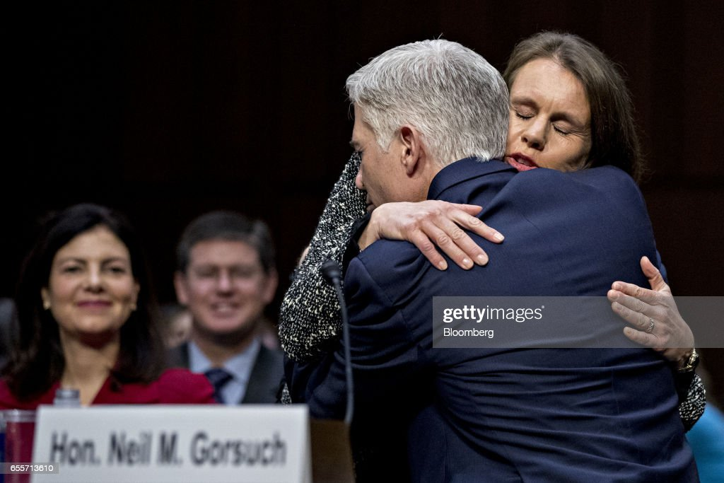 Neil Gorsuch, U.S. Supreme Court nominee for U.S. President Donald Trump, hugs his wife Marie Louise Gorsuch, right, during a Senate Judiciary Committee confirmation hearing in Washington, D.C., U.S., on Monday, March 20, 2017. Gorsuch goes before a Senate committee as a heavy favorite, given Republican control, to win confirmation to a lifetime seat on the nations highest court. Photographer: Andrew Harrer/Bloomberg via Getty Images