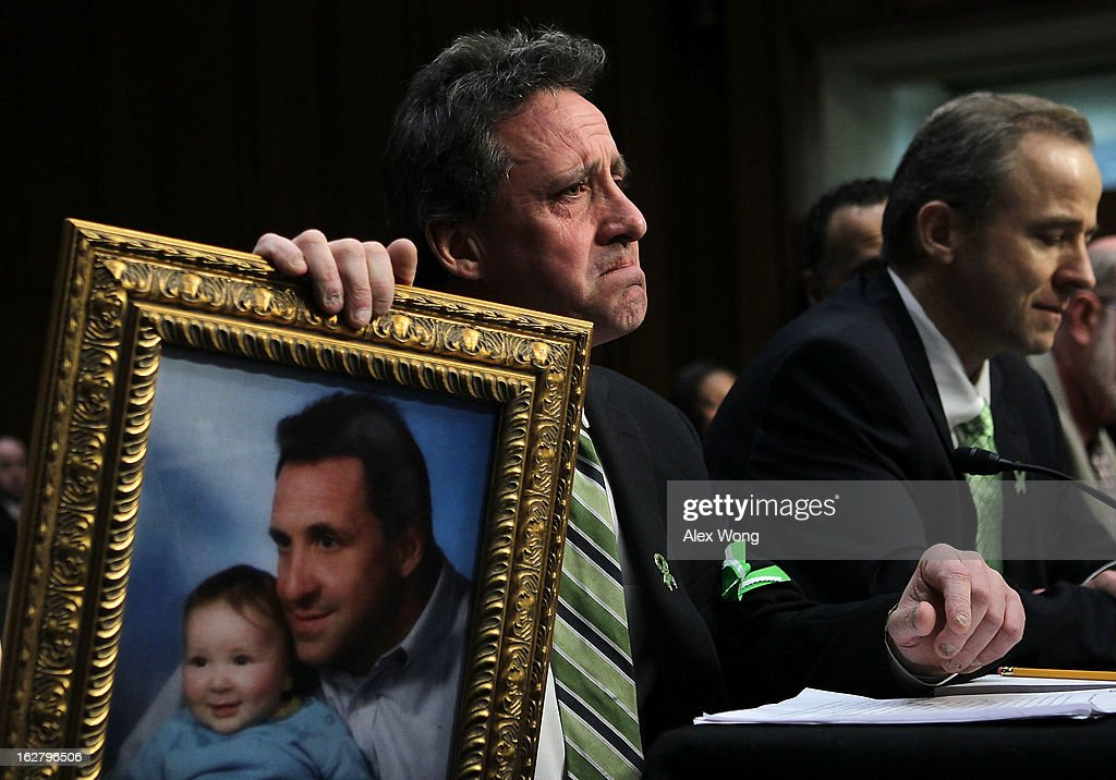 Neil Heslin, father of six-year-old Sandy Hook Elementary School shooting victim Jesse Lewis, holds a picture of him with Jesse as he testifies during a hearing before the Senate Judiciary Committee February 27, 2013 on Capitol Hill in Washington, DC. The committee held a hearing on 'The Assault Weapons Ban of 2013.' EMS medical director of the Western Connecticut Health Network William Begg (R) also testified in the hearing.