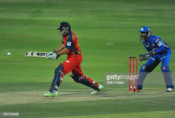 Neil McKenzie of the Lions sweeps as wicketkeeper Dinesh Karthik of the Indians looks on during the Karbonn Smart CLT20 match between Highveld Lions...