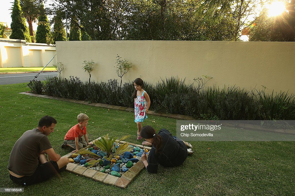 Neil Morris (L) and his son Luke Morris, 5, and Lisa Kolman (R) and her daughter Lindy Kolman, 5, leave goodwill messages written on stones inside planters outside of former South Africa President Nelson Mandela's residence April 1, 2013 in Johannesburg, South Africa. Mandela, 94, is recovering from pneumonia in hospital, his third stay in the last four months. Referring to Mandela by clan name, Madiba, President Jacob Zuma said, 'We appeal to the people of South Africa and the world to pray for our beloved Madiba and his family and to keep them in their thoughts.' Mandela's lungs were damaged when he contracted tuberculosis during his 27 years in the infamous Robben Island prison. Mandela became the nation's first democratically elected president in 1994 following the end of apartheid.
