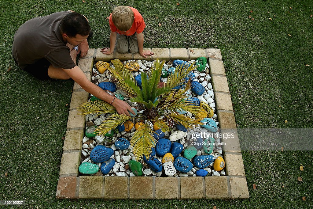 Neil Morris (L) and his son Luke Morris, 5, leave a goodwill message written on a stone inside a planter outside of former South Africa President Nelson Mandela's residence April 1, 2013 in Johannesburg, South Africa. Mandela, 94, is recovering from pneumonia in hospital, his third stay in the last four months. Referring to Mandela by clan name, Madiba, President Jacob Zuma said, 'We appeal to the people of South Africa and the world to pray for our beloved Madiba and his family and to keep them in their thoughts.' Mandela's lungs were damaged when he contracted tuberculosis during his 27 years in the infamous Robben Island prison. Mandela became the nation's first democratically elected president in 1994 following the end of apartheid.
