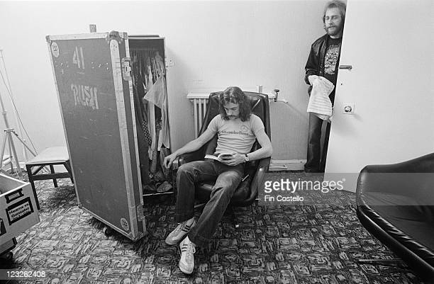 Neil Peart drummer with Canadian rock band Rush sitting backstage in armchair reading a book beside a travel wardrobe with the door ajar at the...