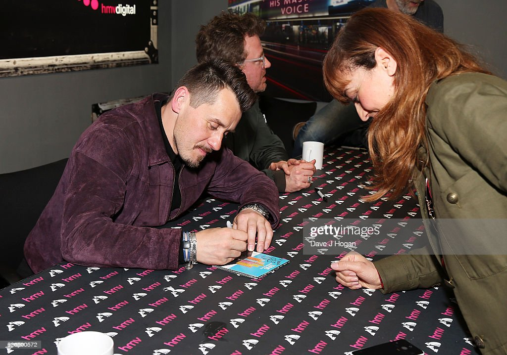 Neil Primrose of Travis meets a fan after performing songs from the new album 'Everything At Once' at HMV Oxford Street on April 30, 2016 in London, England.