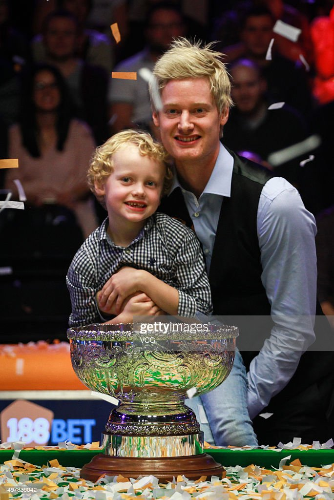 Neil Robertson of Australia celebrates with his son and trophy after final match against Mark Allen of Northern Ireland on day six of Champion of Champions 2015 at Ricoh Arena on November 15, 2015 in Coventry, United Kingdom.