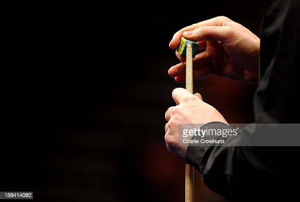 Neil Robertson of Australia chalks his cue during his first round match against Ding Junhui of China at Alexandra Palace on January 13 2013 in London...