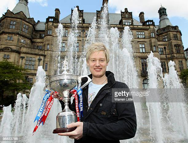 Neil Robertson of Australia poses with the trophy at a photocall after beating Graeme Dott of Scotland to win the Betfredcom World Snooker...