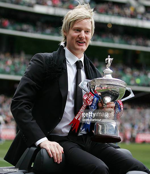 Neil Robertson of Australia shows the trophy he won at the World Snooker Championships to the crowd before the round 16 AFL match between the...