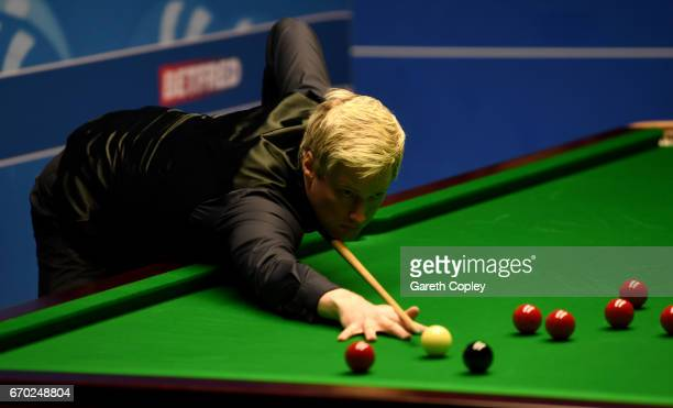 Neil Robertson plays a shot against Noppon Saengkham during their first round match of the World Snooker Championship at Crucible Theatre on April 19...