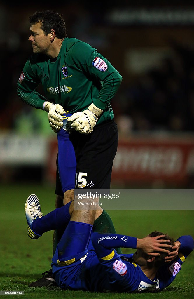 Neil Sullivan of AFC Wimbledon helps his team mate Chris Hussey during the npower League Two match between AFC Wimbledon and Port Vale at The Cherry Red Records Stadium on January 24, 2013 in Kingston upon Thames, England.
