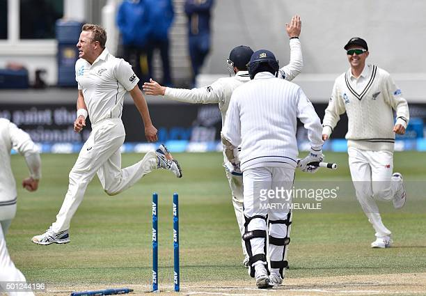 Neil Wagner of New Zealand celebrates bowling Angelo Mathews C captain of Sri Lanka with team mate Trent Boult R during day five of the first...