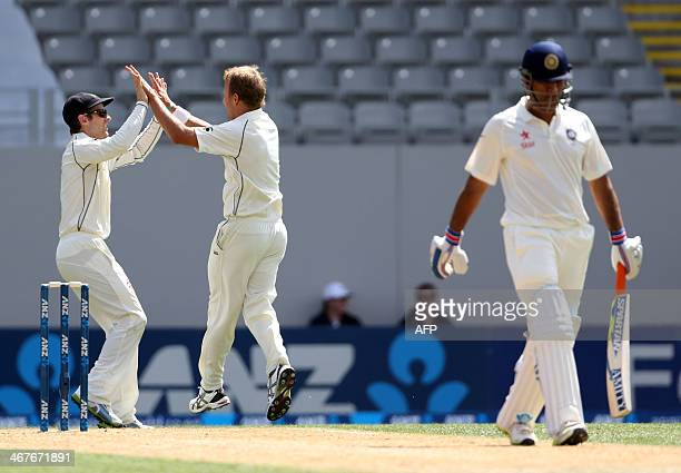 Neil Wagner of New Zealand celebrates with teammate Kane Williamson the wicket of India's MS Dhoni during day two of the international cricket Test...