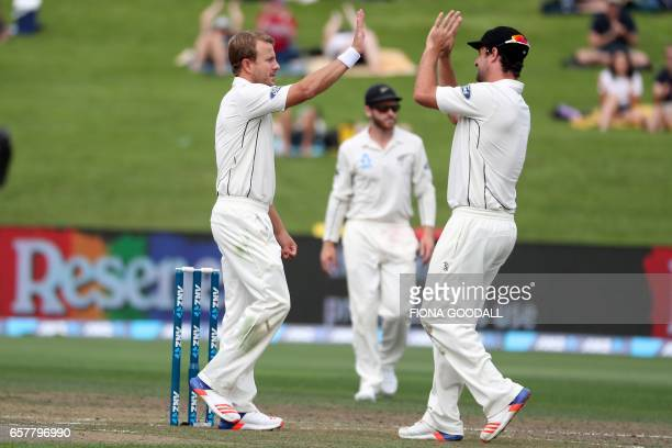 Neil Wagner of New Zealand takes a wicket and celebrates with teammate Colin de Grandhomme on day two of the third Test cricket match between New...