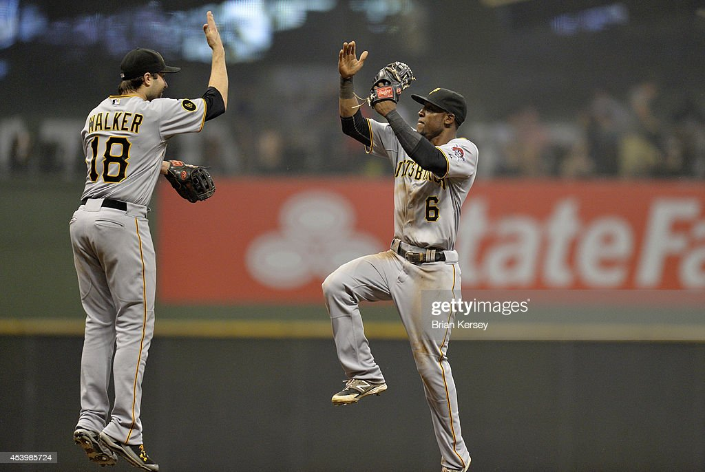 Neil Walker #18 and Starling Marte #6 of the Pittsburgh Pirates celebrate their win over the Milwaukee Brewers at Miller Park on August 22, 2014 in Milwaukee, Wisconsin. The Pirates defeated the Brewers 8-3.