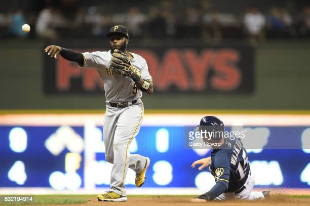 Neil Walker of the Milwaukee Brewers is forced out at second base as Josh Harrison of the Pittsburgh Pirates turns the double play during the eighth...