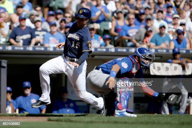 Neil Walker of the Milwaukee Brewers slides into home plate to score a run past Willson Contreras of the Chicago Cubs in the first inning at Miller...