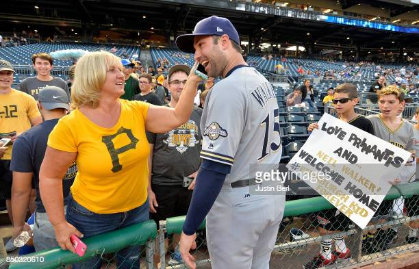 Neil Walker of the Milwaukee Brewers talks to a fan on a cell phone before the start of the game against the Pittsburgh Pirates at PNC Park on...