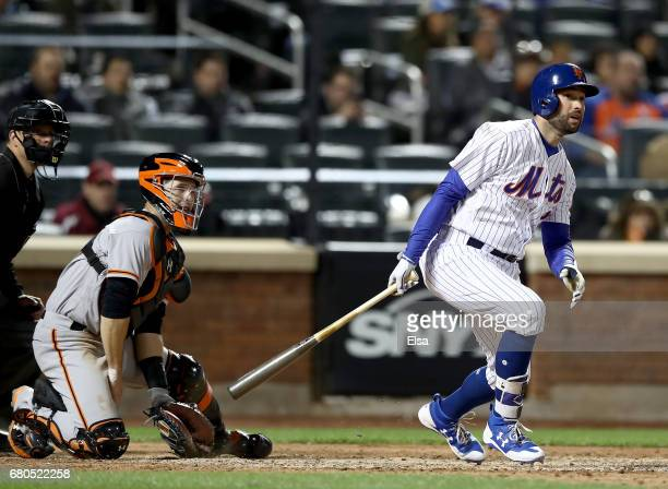 Neil Walker of the New York Mets drives in the game winning run as Buster Posey of the San Francisco Giants defends in the bottom of the ninth inning...