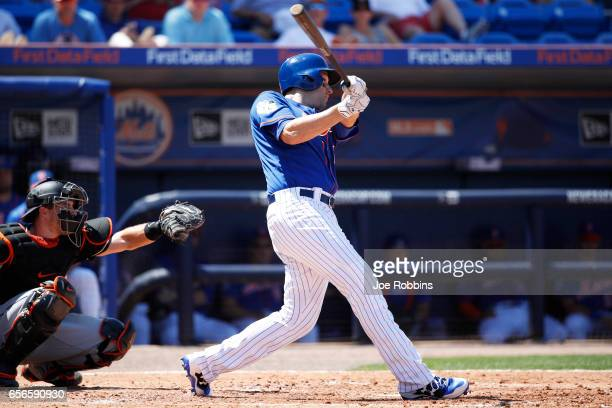 Neil Walker of the New York Mets hits a tworun double in the second inning of a Grapefruit League spring training game against the Miami Marlins at...