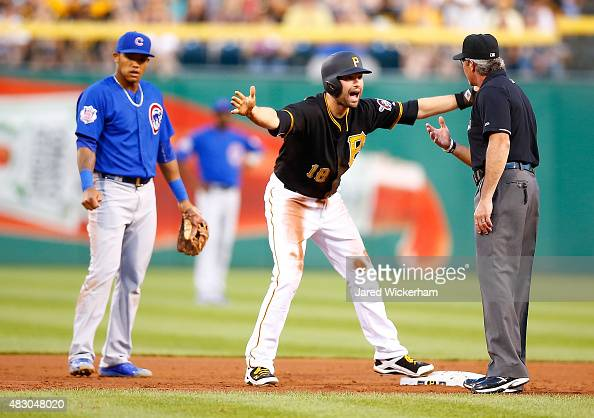 Neil Walker of the Pittsburgh Pirates argues a call with umpire Paul Nauert that he ran out of the base path during a rundown with Addison Russell of...