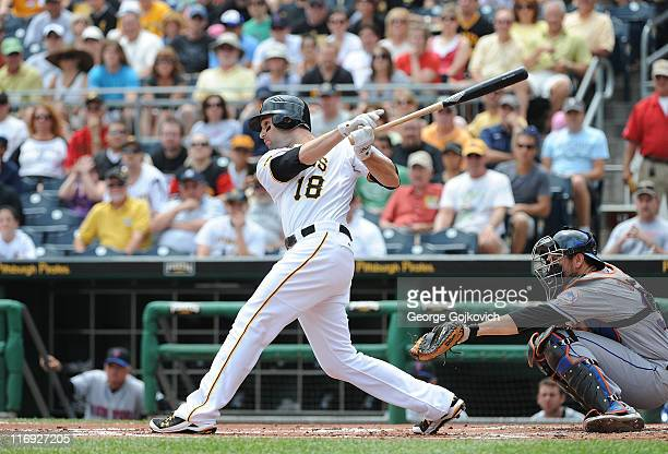 Neil Walker of the Pittsburgh Pirates bats as catcher Josh Thole of the New York Mets looks on during a game at PNC Park on June 12 2011 in...