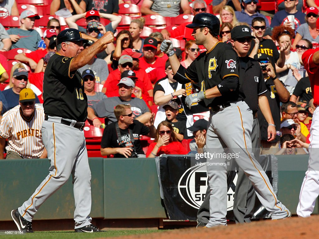 Neil Walker #18 of the Pittsburgh Pirates celebrates his RBI triple with third base coach Nick Leyva #16 against the Cincinnati Reds at Great American Ball Park on September 27, 2014 in Cincinnati, Ohio.