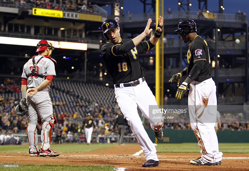 Neil Walker #18 of the Pittsburgh Pirates celebrates with <a gi-track='captionPersonalityLinkClicked' href=/galleries/search?phrase=Starling+Marte&family=editorial&specificpeople=7934200 ng-click='$event.stopPropagation()'>Starling Marte</a> #6 after scoring on a two-RBI single off the bat of Andrew McCutchen (not pictured) in the second inning against the Cincinnati Reds during the game on April 12, 2013 at PNC Park in Pittsburgh, Pennsylvania.