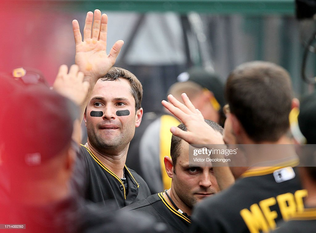 Neil Walker #18 of the Pittsburgh Pirates celebrates with teammates in the dugout after scoring on an error by J.B Shuck #39 of the Los Angeles Angels of Anaheim (not in photo) from a single to left field by Travis Snider #23 (not in photo) in the tenth inning during the MLB game at Angel Stadium of Anaheim on June 23, 2013 in Anaheim, California. The Pirates defeated the Angels 10-9 in ten innings.