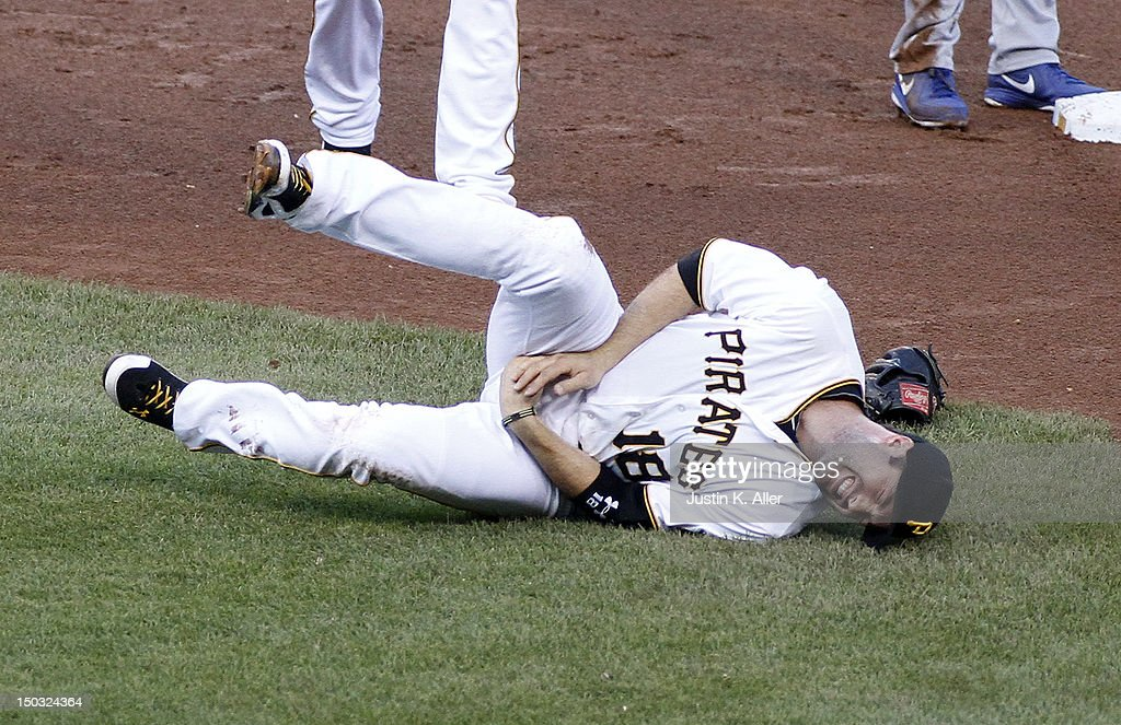 Neil Walker #18 of the Pittsburgh Pirates grimaces in pain after injuring his hand attempting to turn a double play in the first inning against the Los Angeles Dodgers during the game on August 15, 2012 at PNC Park in Pittsburgh, Pennsylvania.