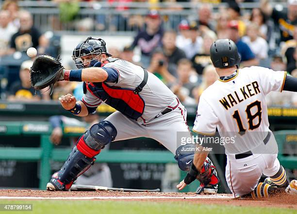 Neil Walker of the Pittsburgh Pirates slides in safe on a RBI single in the first inning during the game against catcher AJ Pierzynski of the Atlanta...