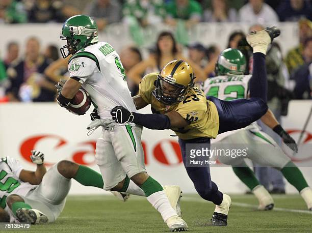 Neil Wilson of the Saskatchewan Rough Riders breaks away from the tackle of Kyries Hebert of the Winnipeg Blue Bombers during the third quarter in...