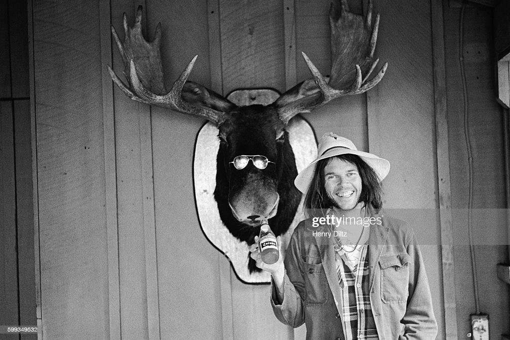 Neil Young holds a beer bottle under the mouth of a stuffed moose head wearing sunglasses in Malibu, California.