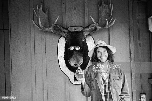 Neil Young holds a beer bottle under the mouth of a stuffed moose head wearing sunglasses in Malibu California